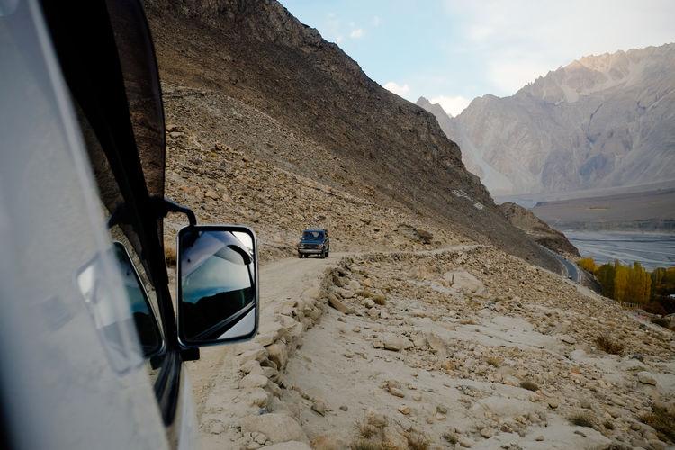 Off-road cars running along unpaved road in karakoram mountain range. gilgit baltistan, pakistan.