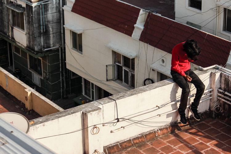 Full length of man standing on railing against buildings