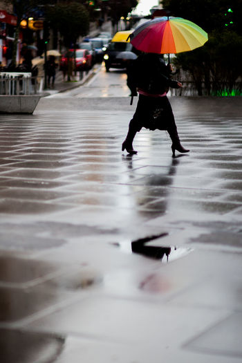 Low Section Of Woman Walking On Wet Footpath In City