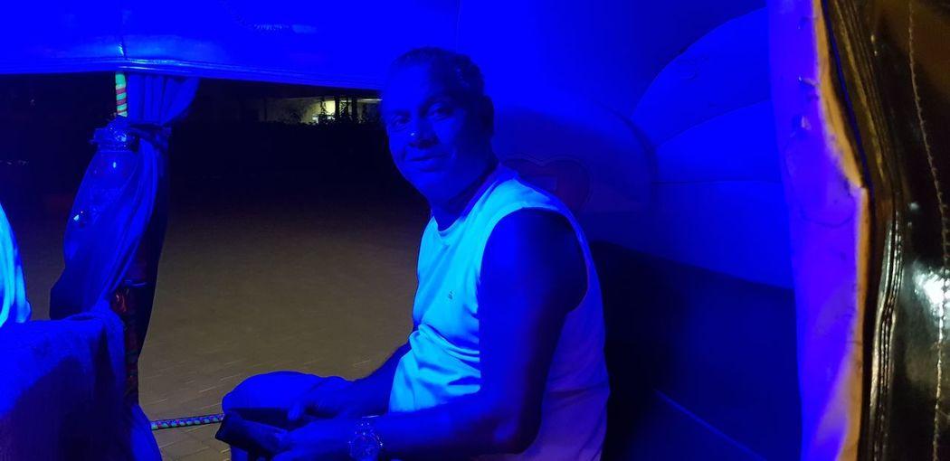Full length of man sitting at illuminated nightclub