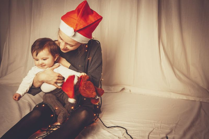 mom and baby christmas time Santa Hat Home White Background Christmastime Mother Light Strings Smiling Christmas Two People Child Childhood Family Emotion Indoors  Love Togetherness Positive Emotion Celebration Christmas Bonding Happiness Offspring Gift Holiday Moments