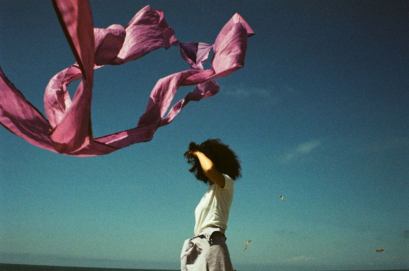 Woman standing by pink flowers against blue sky