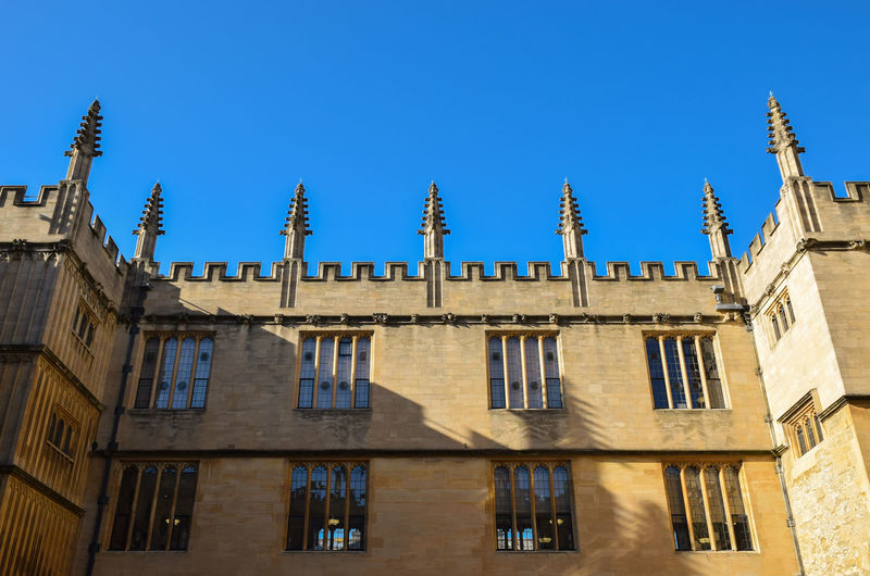 Low angle view of historic university against clear blue sky