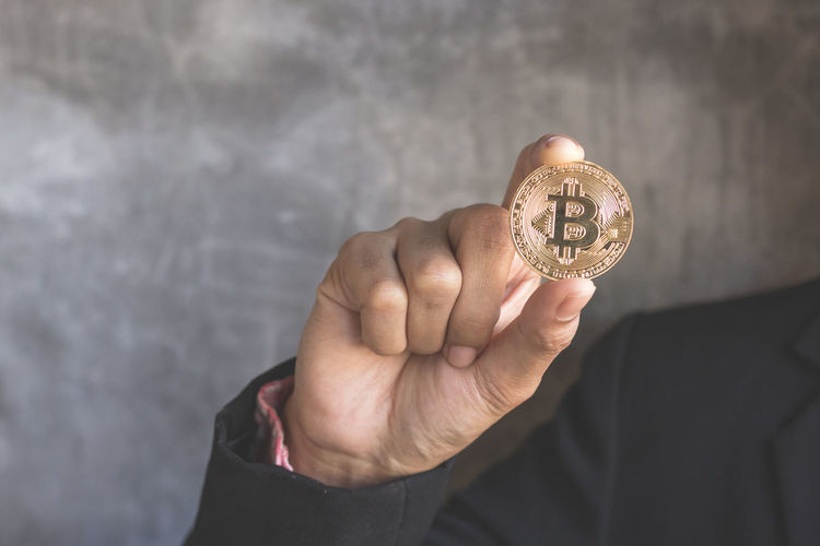 Cropped hands of business person holding bitcoin against wall