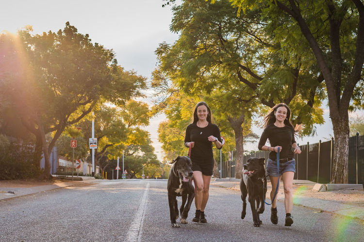 Portrait of smiling sisters with dogs running on road against trees