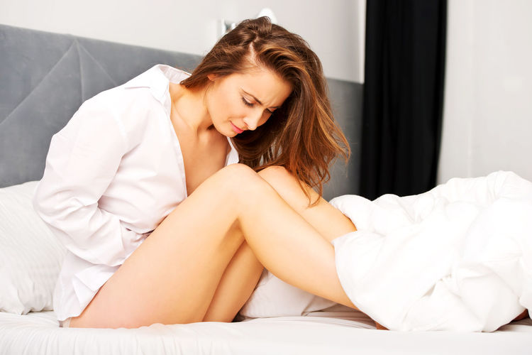 Woman suffering from stomachache while sitting on bed at home