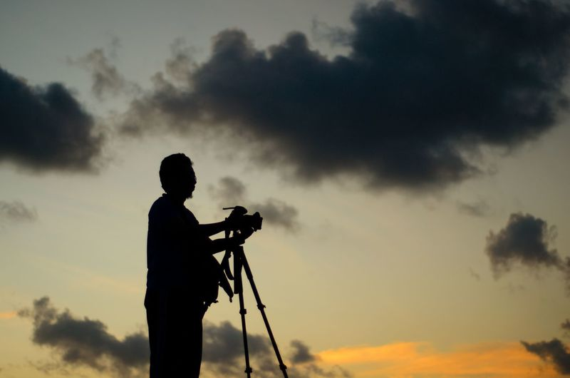 Scenic view of photographer silhoutte on the sunset background. Photography Photography Themes Camera - Photographic Equipment Men Silhouette Standing Filming Full Length Photographing Sky Cloud - Sky Tripod Photographer Camera Digital Camera
