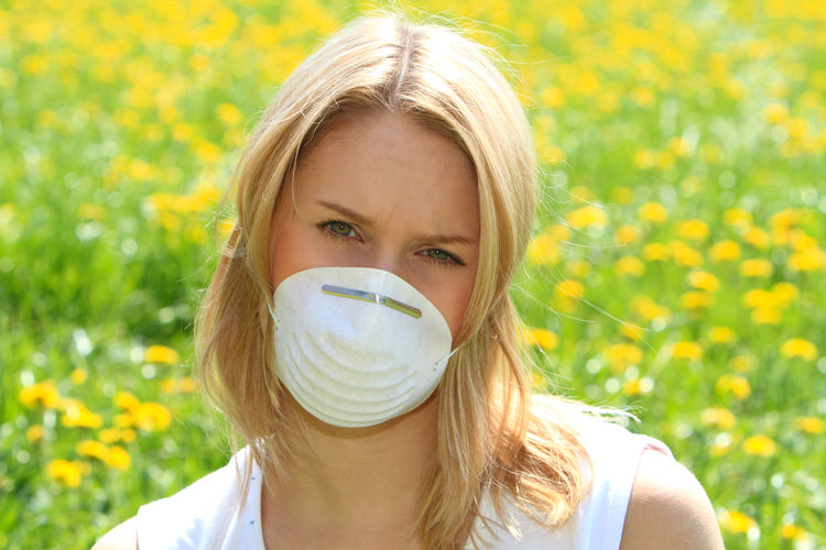 young woman protects herself with a respiratory mask against pollen allergy Nature Woman Allergy Girl Healthcare And Medicine Illness Lifestyles Mask Painful Pollen Pollen Allergy Portrait Protection Respiratory Mask Sick Sickness Spring Time Summer