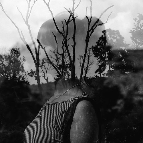 Low section of woman with bare tree against sky