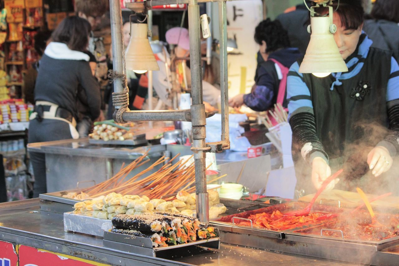 food, food and drink, real people, freshness, market, incidental people, preparation, heat - temperature, men, for sale, market stall, retail, barbecue, smoke - physical structure, burning, meat, outdoors, women, one person, healthy eating, day, ready-to-eat, people