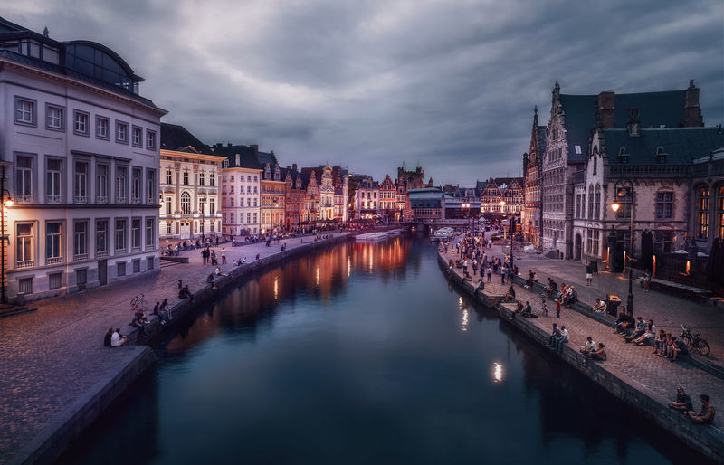 Canal amidst illuminated city buildings against sky