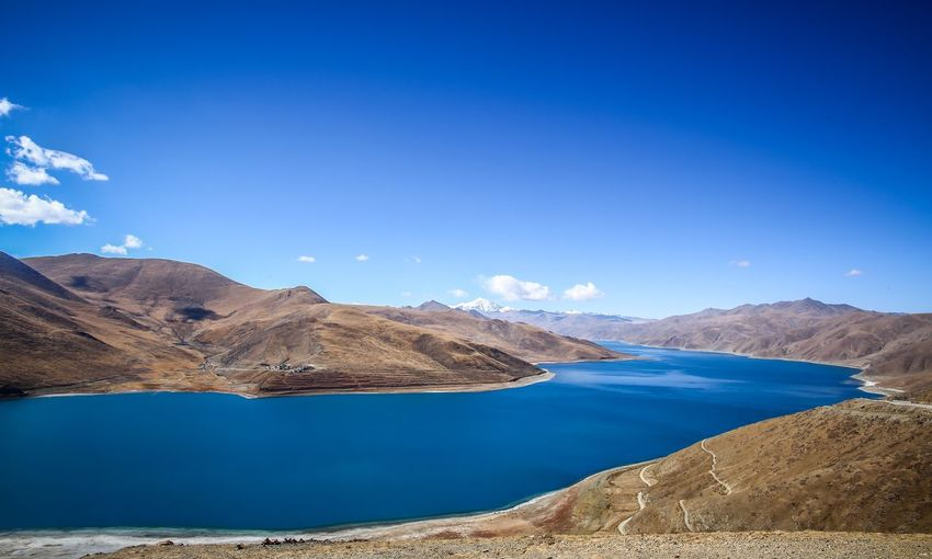 Panoramic view of lake and mountains against blue sky