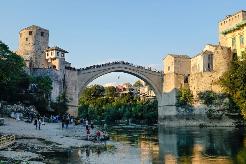 Jump! Man diving off Mostar Bridge into river Bosnia And Herzegovina Diving Mostar Bridge Mostar Diving Riverside Spectators Arch Architecture Bridge - Man Made Structure Built Structure Day Dive Drop Jumping Large Group Of People Real People River Spectator Stari Most Water Waterfront