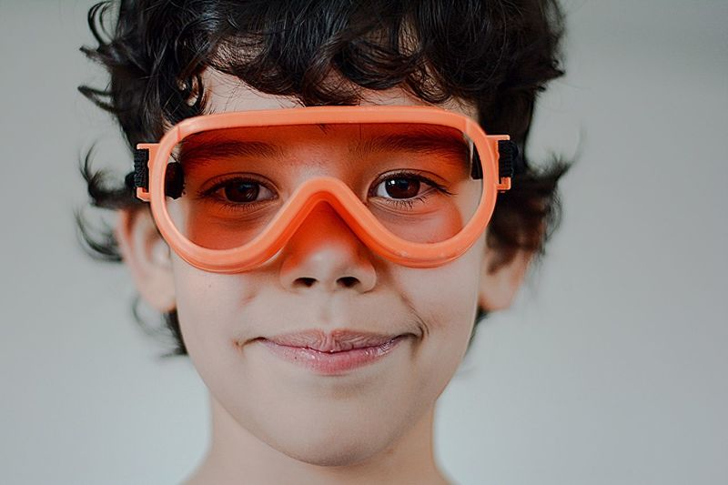 Close-Up Portrait Of Boy Wearing Orange Goggles Against Wall