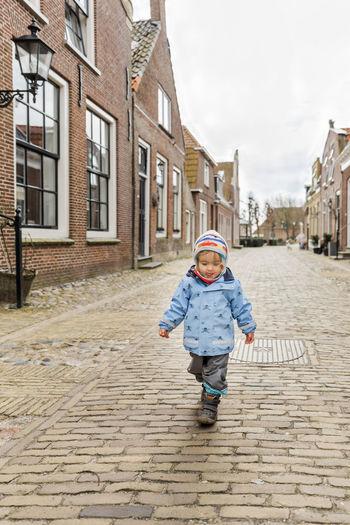 Full Length Of Baby Girl Walking On Street In Town