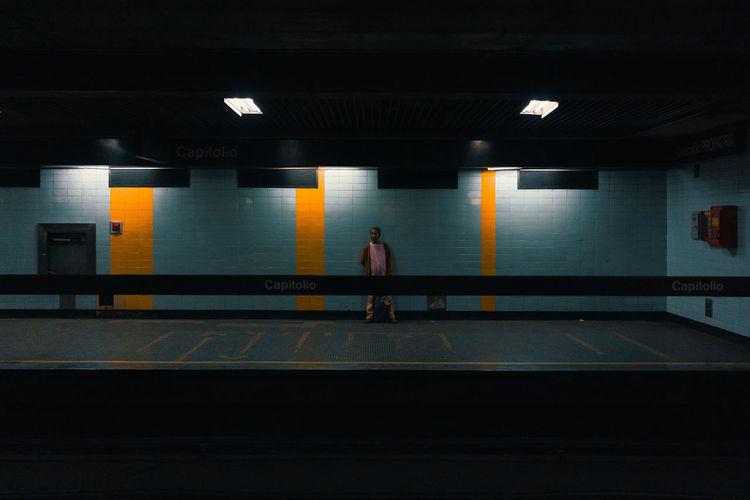 Rear view of man walking on illuminated railroad station platform