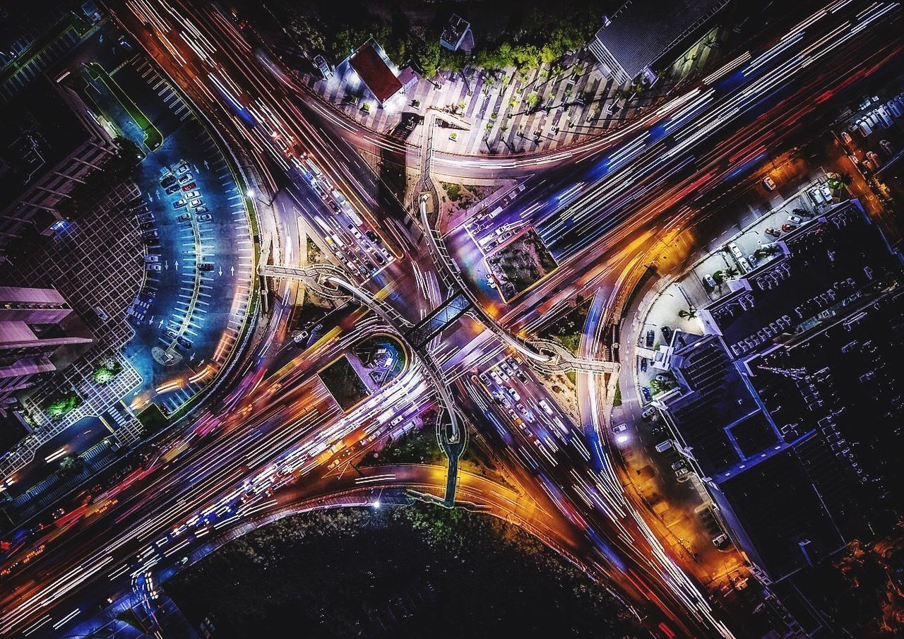 light trail, speed, motion, traffic, long exposure, illuminated, night, high angle view, road, transportation, city, aerial view, elevated road, architecture, city life, connection, blurred motion, street, street light, cityscape, no people, outdoors, building exterior, built structure, modern, high street, travel destinations, rush hour, futuristic