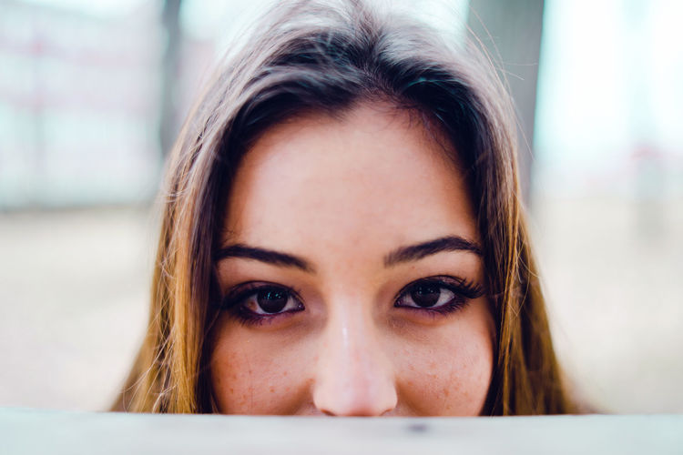 Close-up portrait of beautiful woman hiding by retaining wall