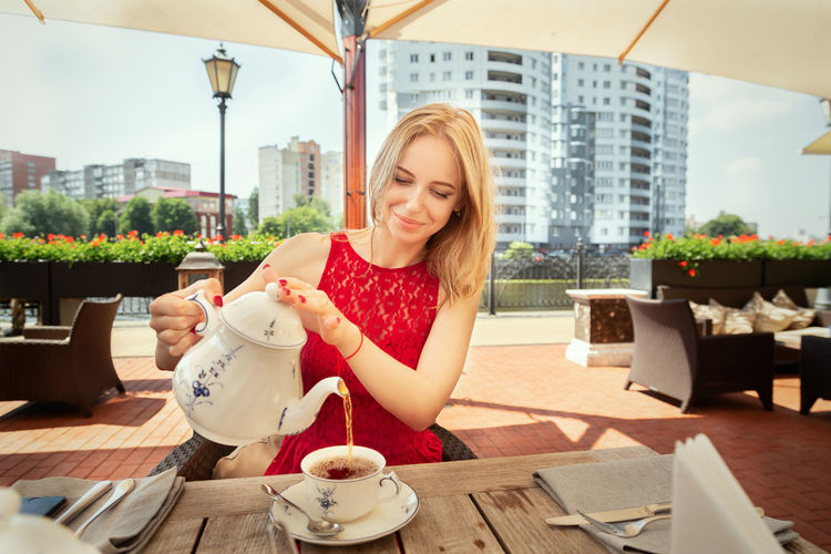 Smiling young woman sitting at table