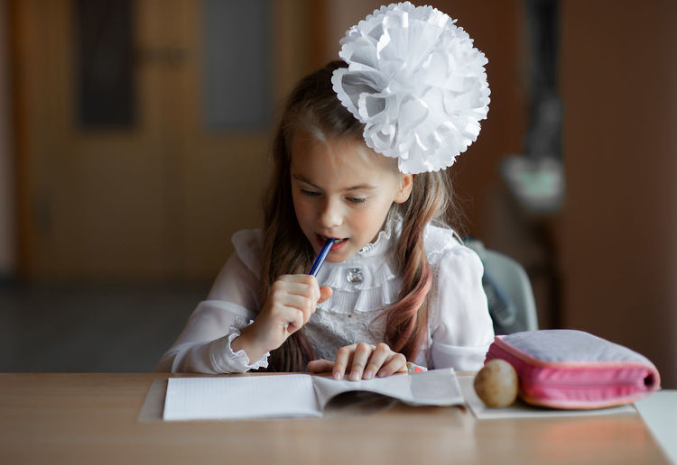Cute girl studying while sitting by table at home