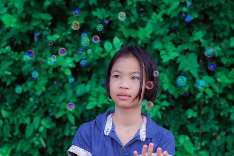 Girl looking at bubbles while standing outdoors
