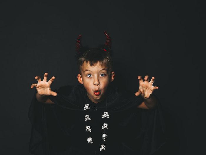Portrait Of Boy Gesturing Against Black Background