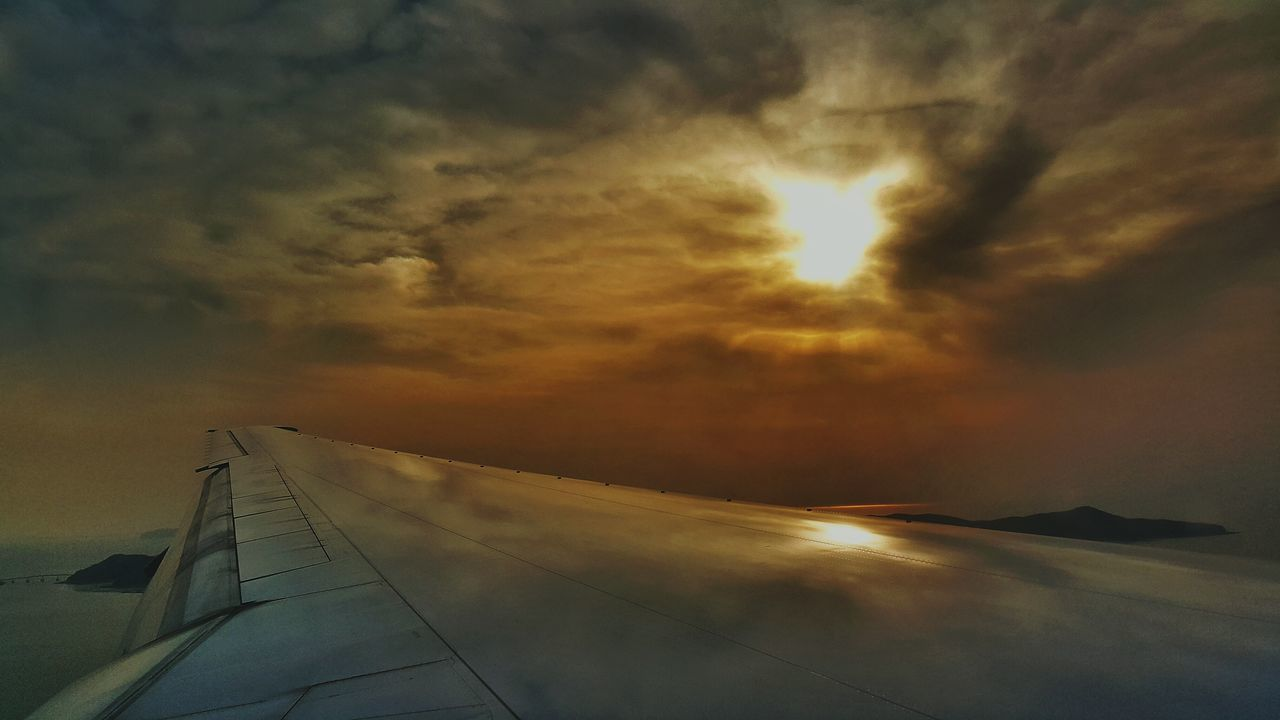 Close-Up Of Aircraft Wing Against Cloudy Sky