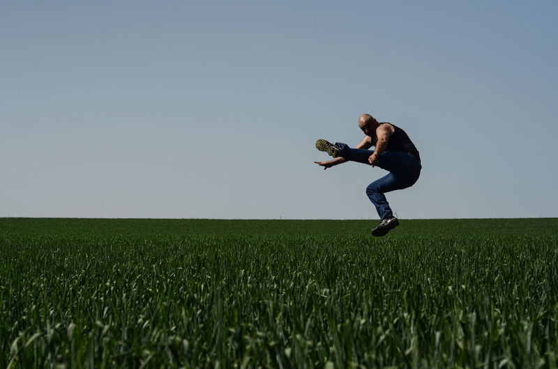 Full Length Of Bald Man Kicking In Mid-Air Over Agricultural Field