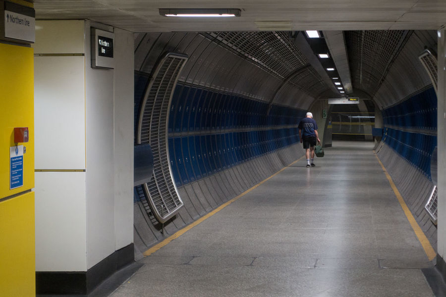 The Long Walk London Bridge Underground Underground Station  Architecture Built Structure Ceiling Converging Lines Diminishing Perspective Direction Flooring Full Length Illuminated Indoors  Lifestyles Lighting Equipment Men Motion One Person Public Transportation Real People Rear View The Way Forward Transportation Travel Walking