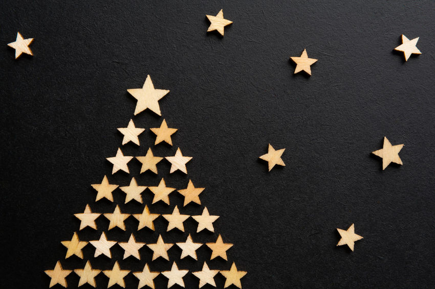 Small wooden decorative craft stars form a christmas tree against dark background with stars, as a christmas - new year's eve concept Star Shape Decoration Celebration Holiday Christmas New Year's Eve Design Bright Wishes Greeting Card Glowing Snow Stars Festive New Year December christmas tree Merry Christmas Copy Space Wooden Golden Falling Flakes Night