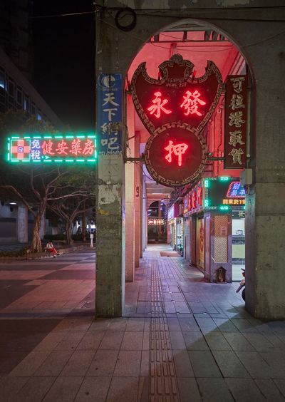 Illuminated street lights on footpath by building at night