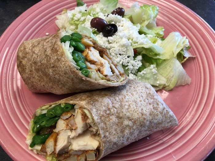 Close-up of chicken wrap with salad on plate