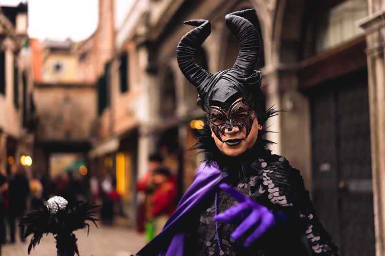 Portrait of man in devil costume at street during carnival