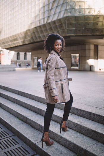 Beautiful african american young woman with afro in a stylish coat, smiling. urban street portrait