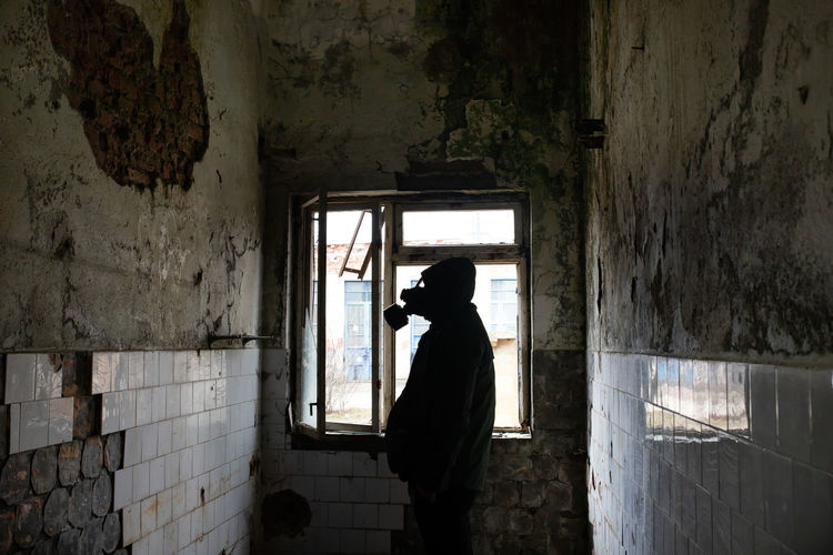 Side view of silhouette man wearing gas mask standing in abandoned house