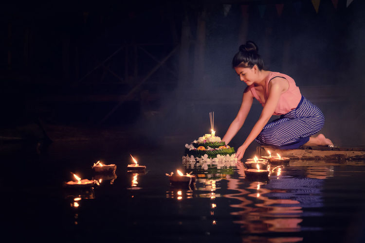 Young Woman In Traditional Clothing Kneeling By Lake At Night