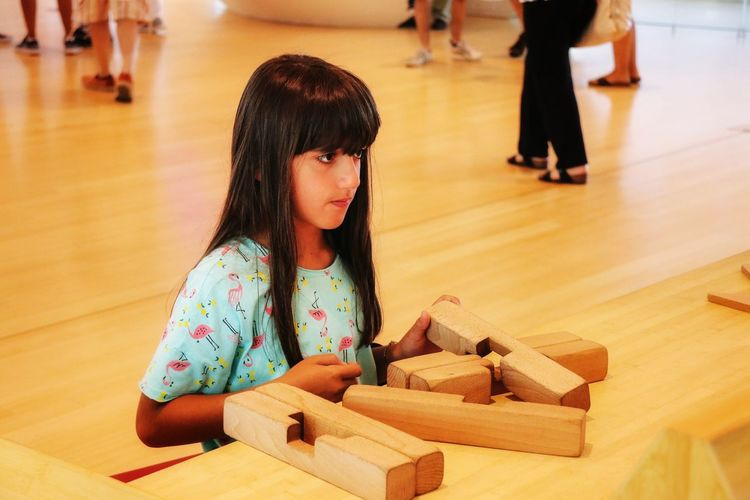 Cute girl looking away at wooden table