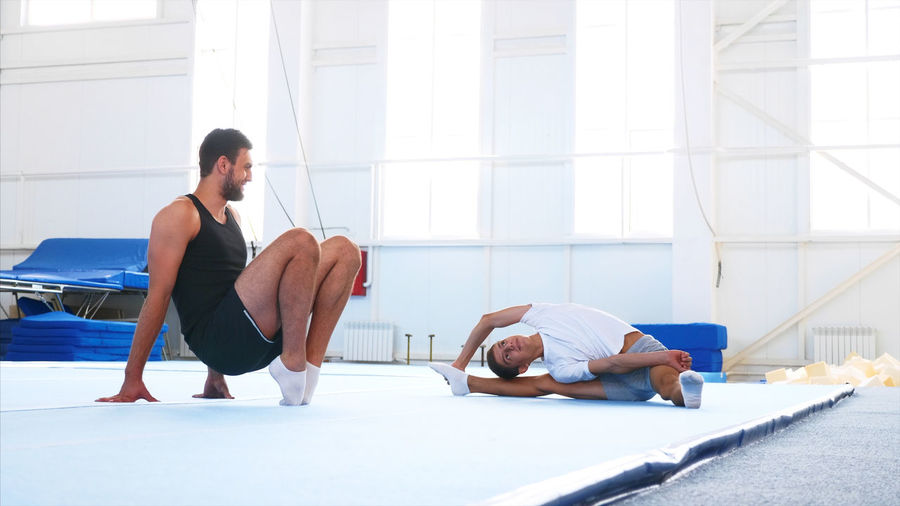 Instructor with teenage boy practicing gymnastics in club