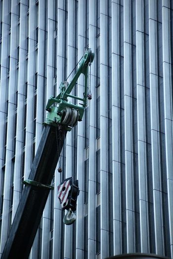 Low angle view of construction equipment against modern skyscrapers