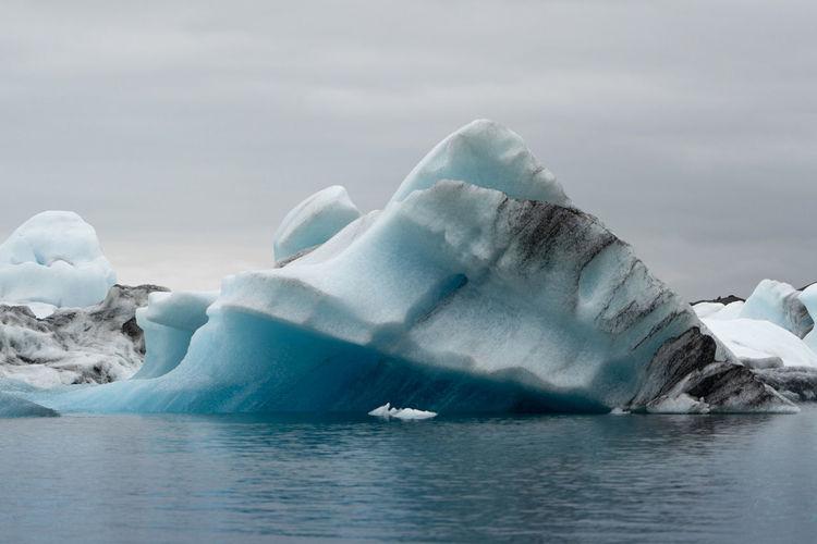 Close-Up Of Icebergs On Sea Against Sky