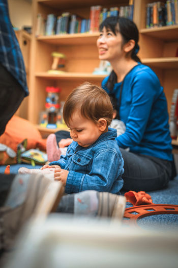 Babyboy Blonde Library London Sitting Baby Boy Babyhood Blue Boys Childhood Day Denim Full Length Home Interior Indoors  Leisure Activity Lifestyles Multi Colored Playground Playing Real People Sitting Two People Business Stories