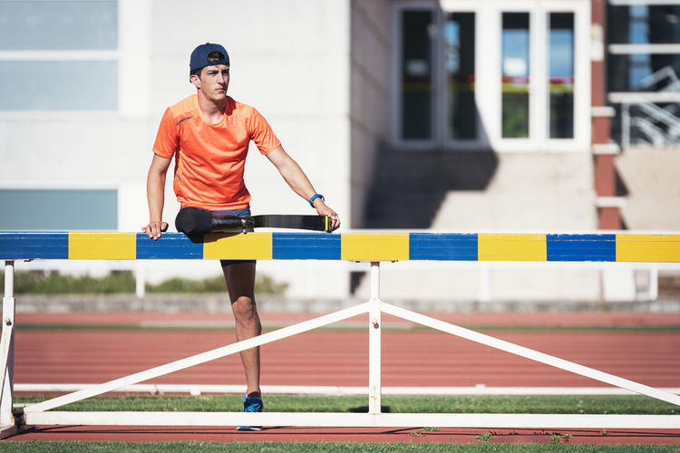 Young athlete with prosthetic leg standing by railing on running track