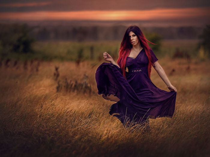 Portrait of woman wearing dress while standing on land during sunset