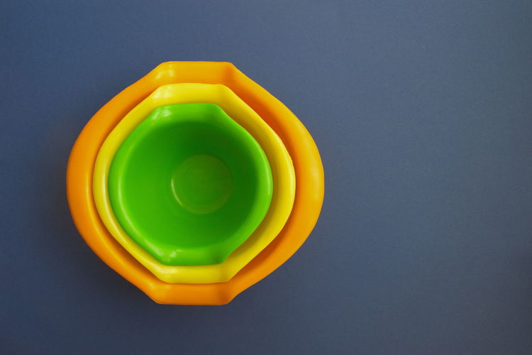 Multi Colored Studio Shot Indoors  Plastic Close-up No People Still Life Directly Above Shape Yellow Circle Colored Background Copy Space High Angle View Green Color Blue Background Orange Color Bowl
