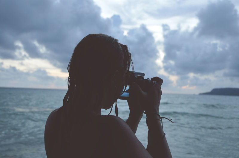 Woman photographing calm sea