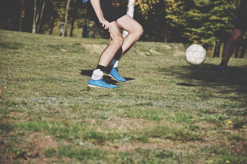 Low section of man playing soccer on field