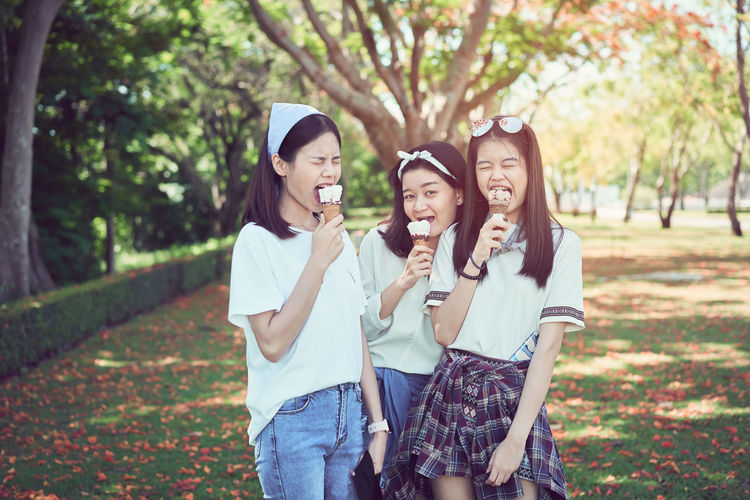Young girl is eating ice cream and happy. At the time of relaxation. Smiling Friendship Happiness Emotion Togetherness Young Adult Leisure Activity Women Casual Clothing Three Quarter Length Young Women Tree Lifestyles Adult Plant Fun Enjoyment Group Of People Front View Teenager Outdoors Positive Emotion