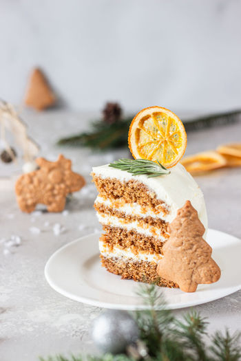 Christmas or new year gingerbread cake decorated with cookies, spices and dried orange slice.