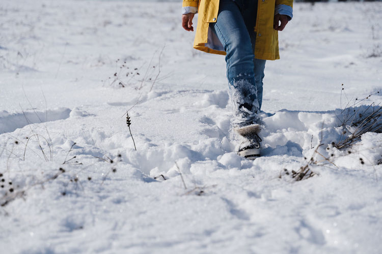 Low section of person standing on snow covered land