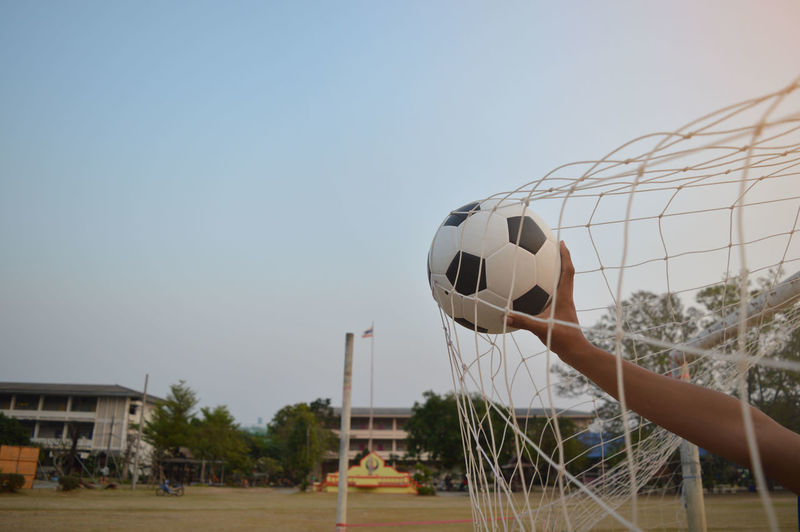 People playing soccer ball against clear sky